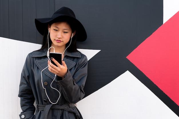 Молодая азиатская женщина с наушниками смотрит ее телефон