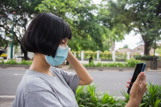 公共の場で携帯電話を使用してフェイスマスクを持つ若いアジアの女性コロナウイルスの概念