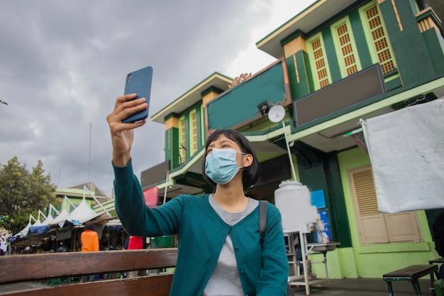 公共の場で携帯電話の自分撮りを使用してフェイスマスクを持つ若いアジアの女性