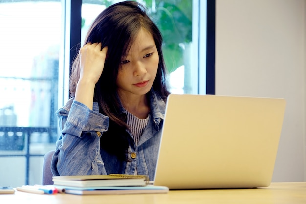 Young asian woman with frustrated expression while working with laptop