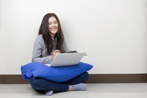 部屋に座っている眼鏡とラップトップを持つ若いアジアの女性。幸せなスマイリーフェイス。