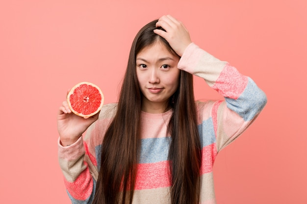 Young asian woman with a grapefruit being shocked, she has remembered important meeting.