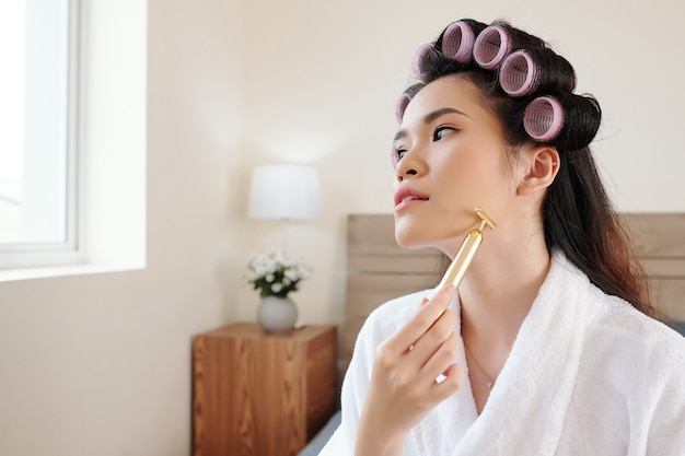 Young asian woman with hair rollers massaging face with roller to tighten skin, cools and soothe it