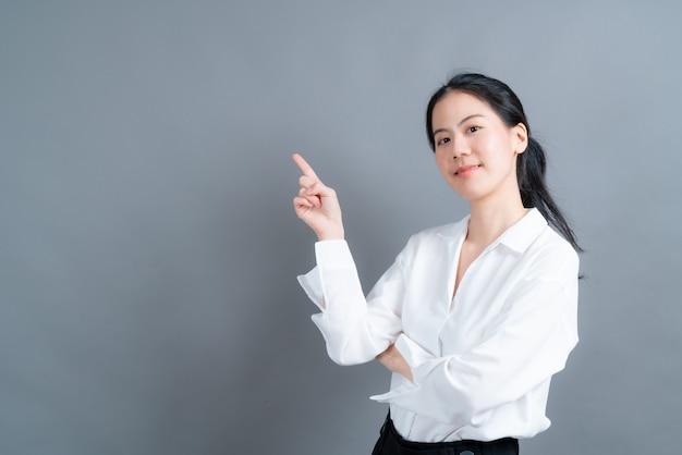 측면에 제시하는 손으로 젊은 아시아 여자