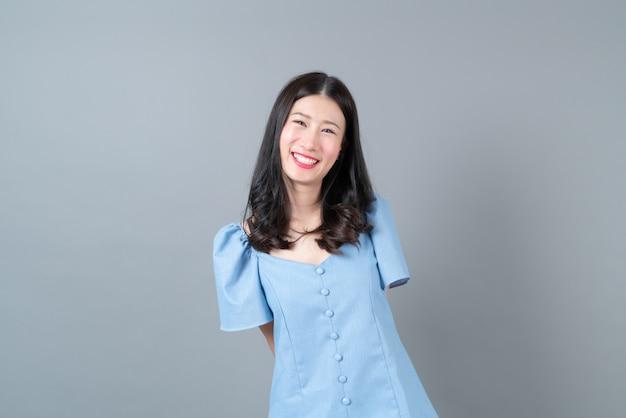 회색에 파란 드레스에 행복하고 웃는 얼굴을 가진 젊은 아시아 여자