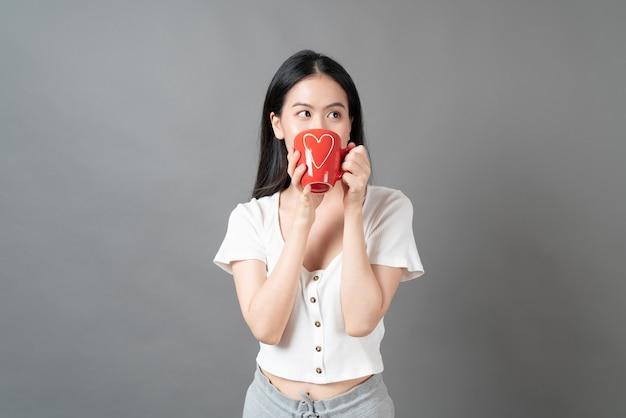 회색 배경에 커피 컵을 들고 행복한 얼굴과 손을 가진 젊은 아시아 여성