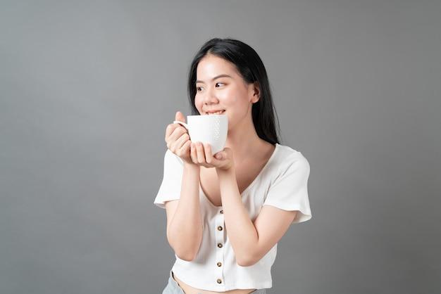 幸せな顔と灰色の壁にコーヒーカップを持っている手を持つ若いアジアの女性