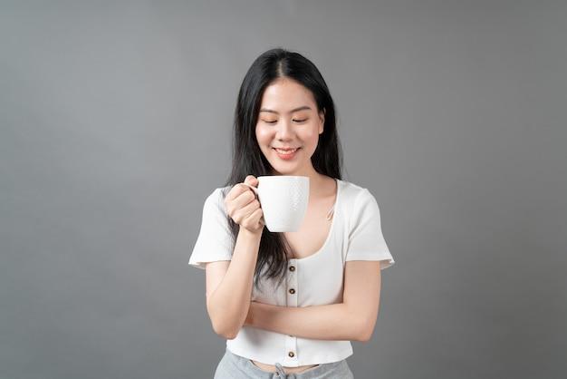 행복 한 얼굴과 손을 잡고 커피 컵 젊은 아시아 여자