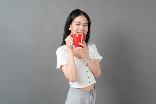 Young asian woman with happy face and hand holding coffee cup on grey background