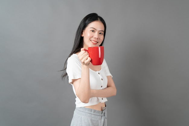 Young asian woman with happy face and hand holding coffee cup on grey wall