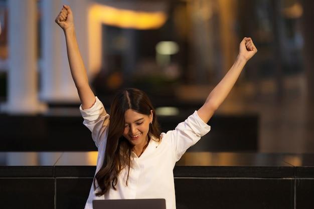 夜の街でラップトップを使用して幸せな叫び驚いた顔を持つ若いアジア女性