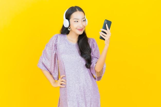노란색에 음악을 듣기위한 헤드폰과 스마트 폰 젊은 아시아 여자