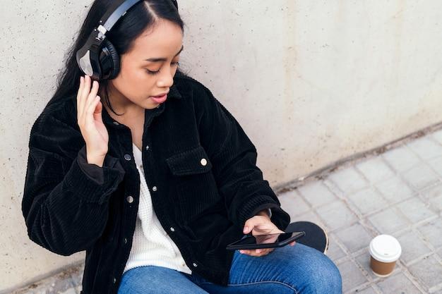 헤드폰을 끼고 있는 젊은 아시아 여성은 휴대전화로 음악을 듣는 것을 즐긴다
