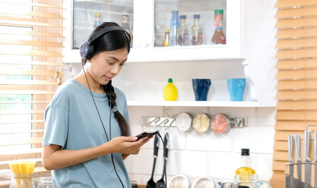 Young asian woman with headphones listening to music from mobile phone at home kitchen