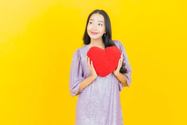 Giovane donna asiatica con cuscino a cuore
