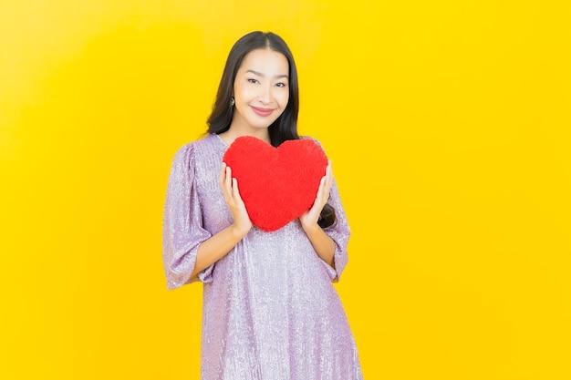 心の枕を持つ若いアジアの女性