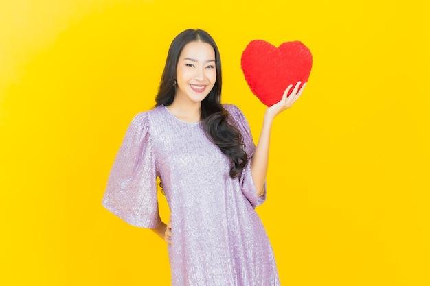 Молодая азиатская женщина с сердечной подушкой