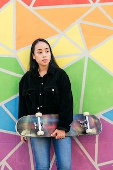 화려한 벽에 기대어 스케이트보드를 탄 젊은 아시아 여성