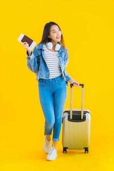 Молодая азиатская женщина с чемоданом и паспортом