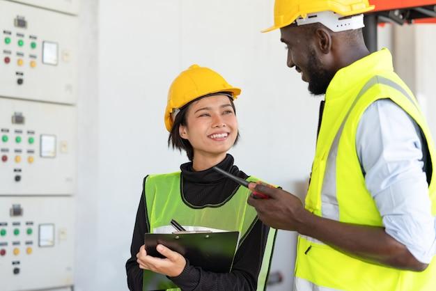 창고 공장에서 선적에서 일하는 안전 조끼와 노란색 헬멧에 남자 노동자와 젊은 아시아 여자