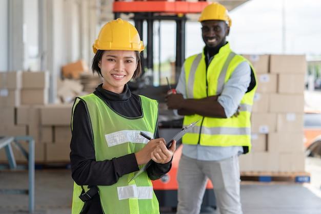 창고 공장에서 작업하는 안전 조끼와 노란색 헬멧에 남자 노동자와 젊은 아시아 여성