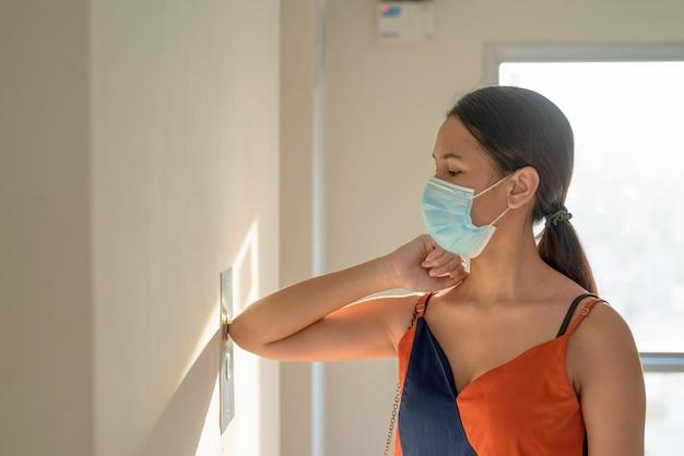 감염을 피하기 위해 팔꿈치로 엘리베이터 문을 누르면 코로나 바이러스 발생으로부터 보호하기위한 마스크와 젊은 아시아 여자