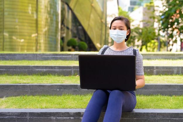 Молодая азиатская женщина с маской для защиты от вспышки вируса короны, используя ноутбук, сидя на открытом воздухе