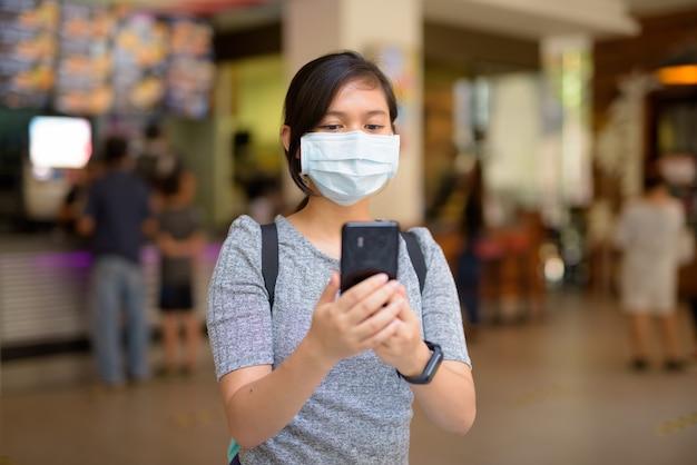 레스토랑 내부에서 전화를 사용하여 코로나 바이러스 발생으로부터 보호하기 위해 마스크를 가진 젊은 아시아 여성