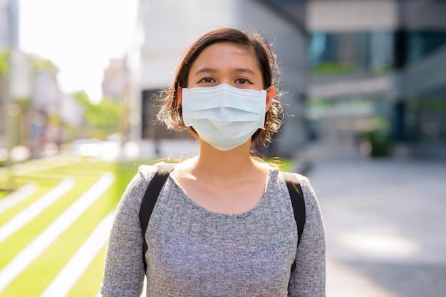 Молодая азиатская женщина с маской для защиты от вспышки коронавируса на открытом воздухе