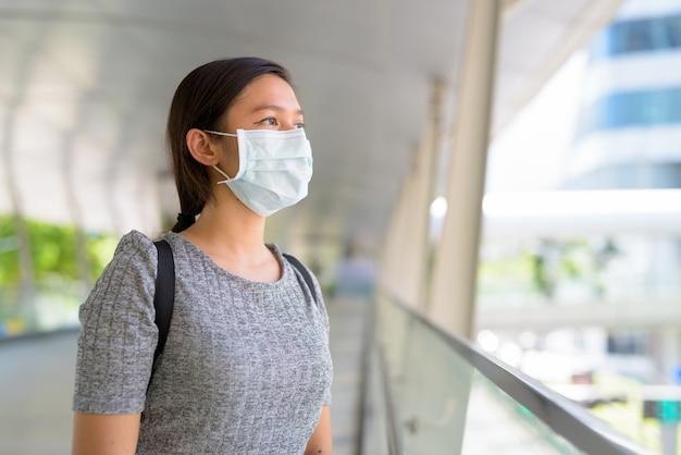 Молодая азиатская женщина с маской думает и смотрит на город