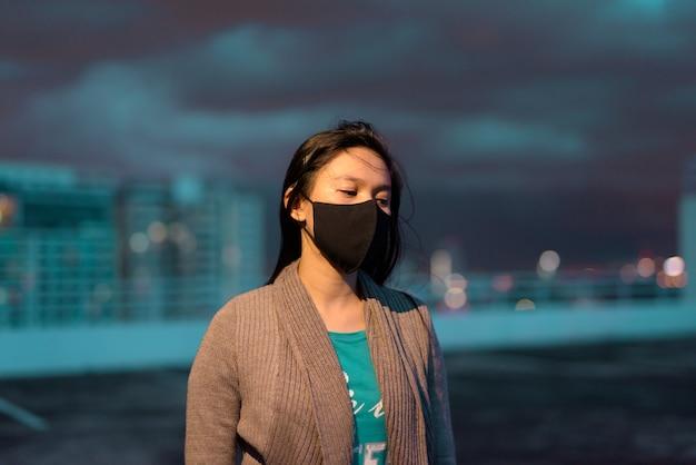 Молодая азиатская женщина с маской думая и смотря вниз во время штормовой погоды на ноче