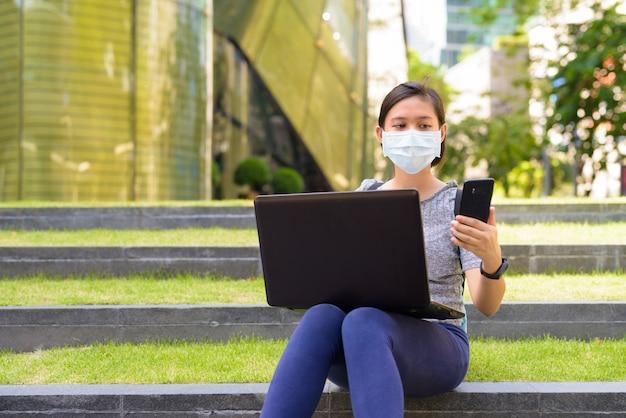 Молодая азиатская женщина с маской, используя телефон и ноутбук, сидя на лестнице на открытом воздухе