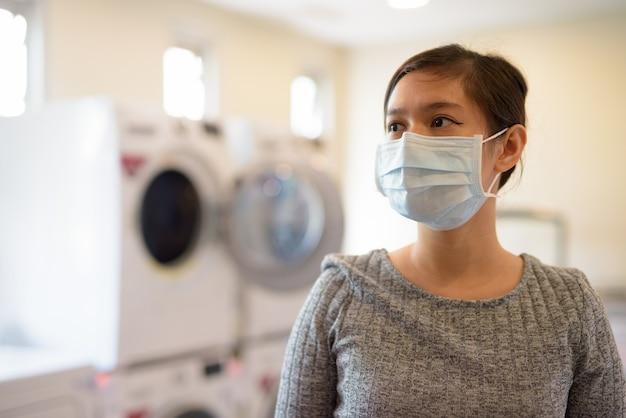 コインランドリーで洗濯を待っているマスクを持つ若いアジアの女性