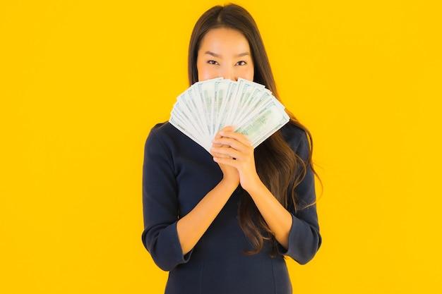 お金を持つ若いアジア女性