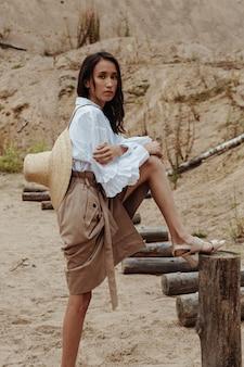 砂浜の風景の中の木の丸太に足でポーズをとる自然の美しさを持つ若いアジアの女性。