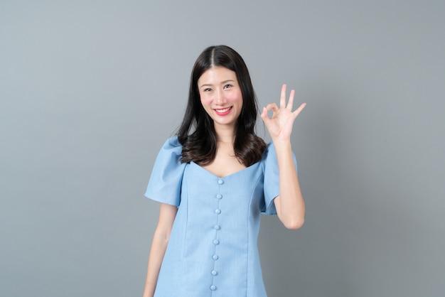 Молодая азиатская женщина с хорошей рукой подписывает синее платье на сером