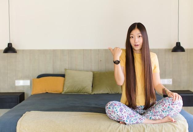 Молодая азиатская женщина с открытым ртом, выглядящая испуганной и шокированной
