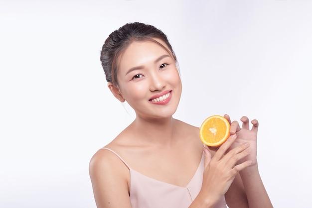 고립 된 그녀의 손에 오렌지와 젊은 아시아 여자