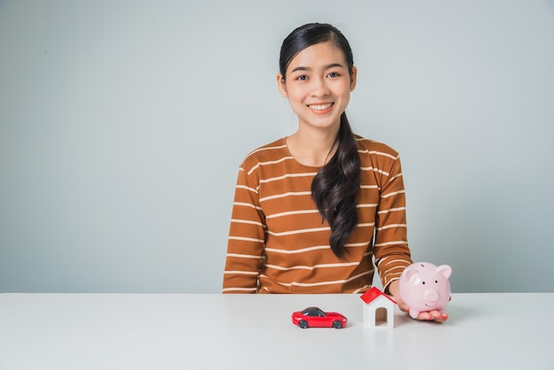 Young asian woman with piggy bank and toy house and car