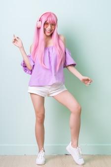緑の背景にポーズをとってピンクの髪を持つ若いアジアの女性