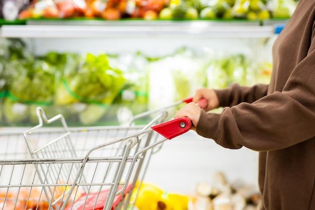 바이러스 covid-19 발발 동안 슈퍼마켓에서 신선한 야채를 구입하기 위해 쇼핑 카트를 밀고 보호 마스크를 가진 젊은 아시아 여성. covid-19 바이러스 예방 개념.