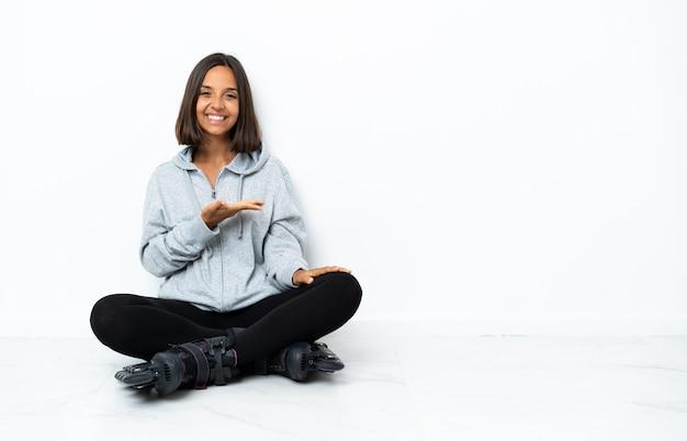 に向かって笑顔を見ながらアイデアを提示する床にローラースケートを持つ若いアジアの女性