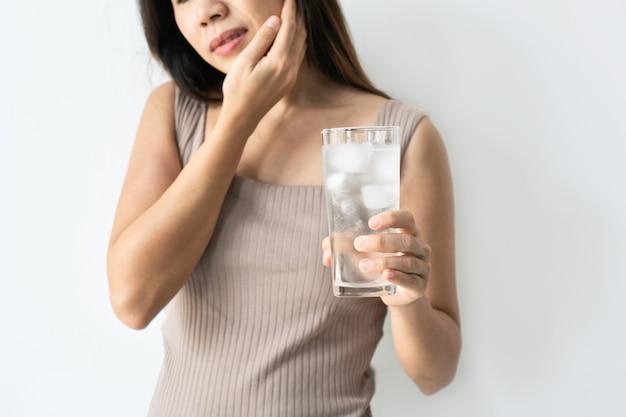 敏感な歯と氷と冷たい水のガラスを持っている手を持つ若いアジアの女性。冷たい飲み物を飲む女の子、角氷でいっぱいのガラスと歯痛、痛みを感じます。ヘルスケアの概念。