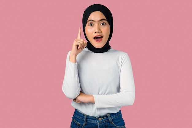Young asian woman with shocked expression and pointing up