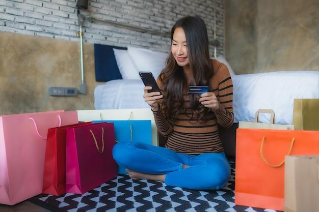 온라인 쇼핑을 위해 신용 카드를 사용하여 스마트 휴대 전화 및 노트북 컴퓨터와 젊은 아시아 여자