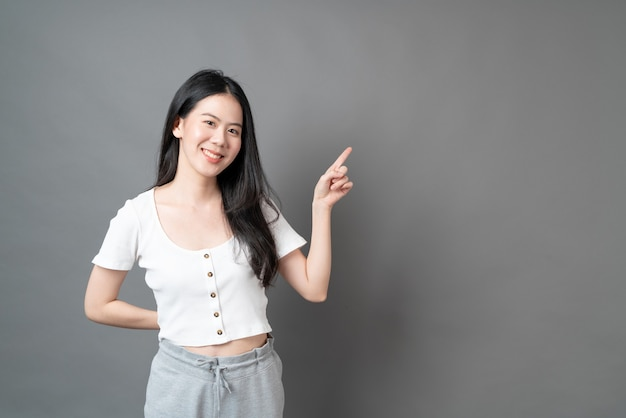 Young asian woman with smiling face and hand presenting on side with grey surface