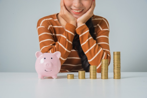 Young asian woman with stack of coins and piggy bank