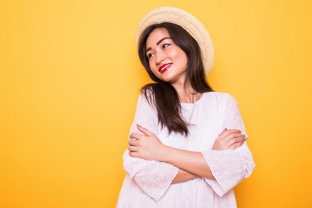 黄色の壁に分離された麦わら帽子を持つ若いアジア女性