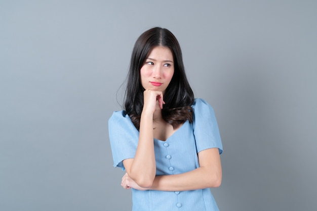 Young asian woman with sulk face in blue dress on grey