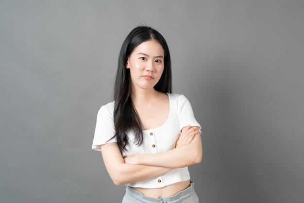 Молодая азиатская женщина с надутым лицом в белой рубашке на серой стене